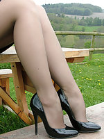 Sexy blonde Iona is posing outdoors on a wooden bench in the countryside, wearing a lovely black pair of stilettos